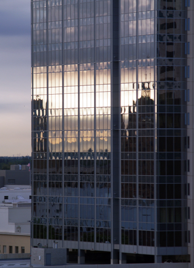 reflection of a bridge in the shiny windows of a modern building in sacramento california