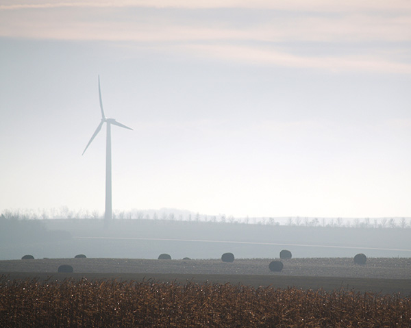 large wind turbines obscured by a hazy day in minnesota