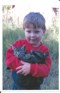 a three year old boy holding his favorite kitten