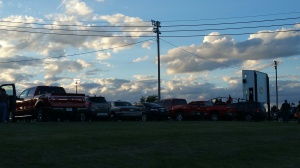 cars parked around football field for high school game