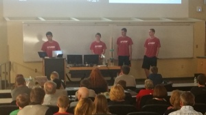 Four boys presenting their water filter design to an audience